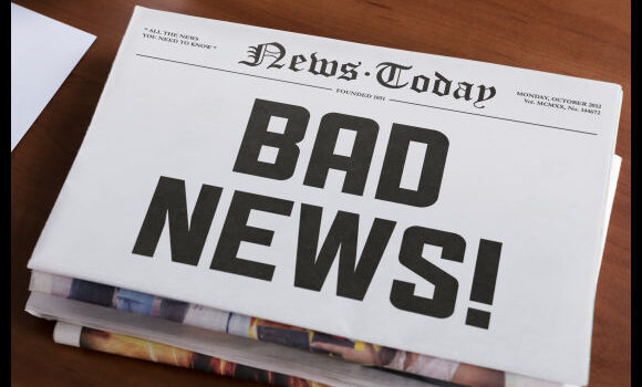"""Newspaper concept with hot topic """"Bad news"""" lying on office desk."""