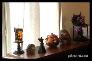 bookshelf with decorations on top--cute cat witch, metal jack o' lantern
